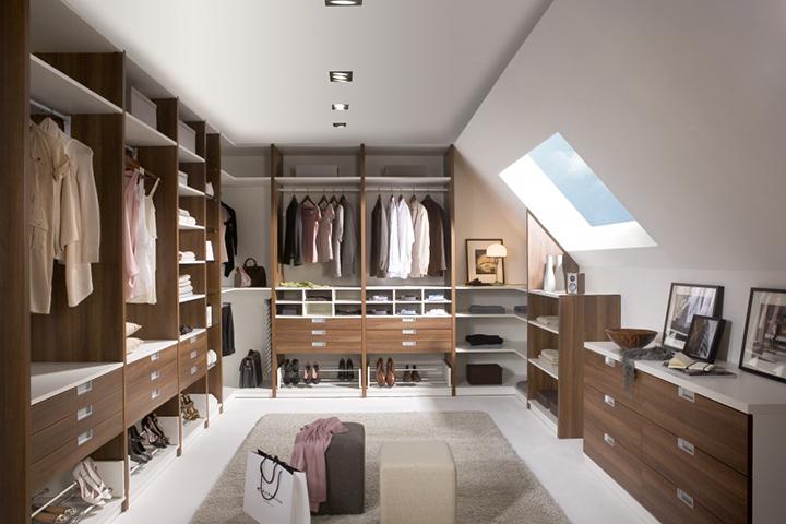 Inloopkasten - Noteborn inloopkast met een open interieur ingedeeld met losse commodekasten, kledingliften, schoenenrekken en een stropdasrek